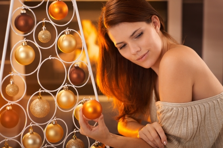 fantasize: Christmas portrait of young hot beauty daydreaming at tree with bulb handheld, smiling, by fireplace.