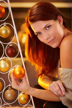 Cosy christmas portrait of smiling beauty by modern christmas tree with bulb handheld, bright light by fireplace. photo