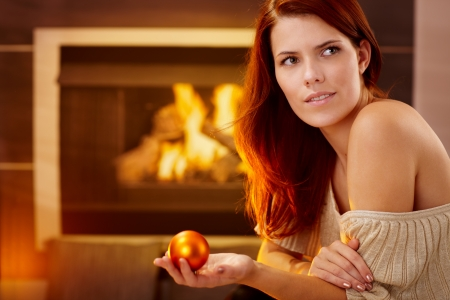 Winter portrait of smiling beauty at fireplace with christmas bulb handheld, looking away. Stock Photo - 15287052