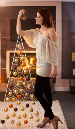 Christmas portrait of pretty woman standing by design tree with star handheld, smiling, daydreaming in cosy living room. photo