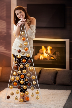Happy attractive woman laughing, standing by design christmas tree at home, by cosy fireplace. photo