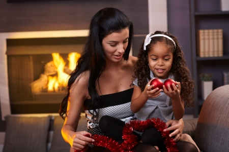 Mother and little daughter at christmas time sitting by fireplace, playing with christmas balls. Stock Photo - 15287024