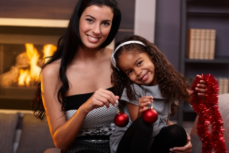 indoor photo: Portrait of beautiful white mother and cute ethnic daughter at christmas time.