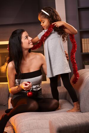 Happy mother and afro little daughter in living room with christmas decoration, smiling. Stock Photo - 15287077