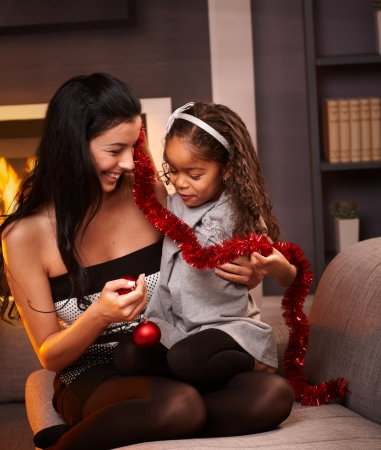 Happy mother and little afro daughter sitting on sofa holding christmas decoration, smiling. photo