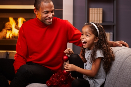 Afro father and beautiful little daughter sitting on sofa with christmas decoration, little girl laughing. photo