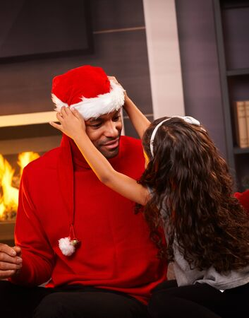 Little girl placing santa hat on fathers head at home. photo