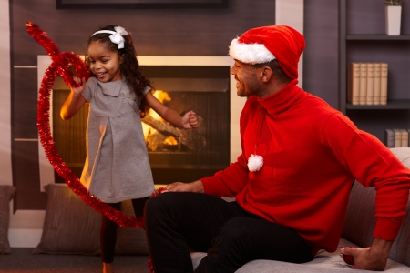 Afro family in christmas mood, father in santa hat, little girl with christmas decorations. photo