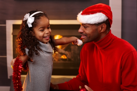 Ethnic father in santa hat, little daughter with christmas decorations at home by fireplace. photo