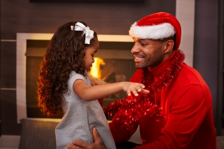 Black father in santa hat and little daughter hugging at home at christmas time. photo