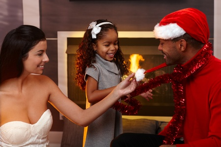 Beautiful mixed race family celebrating christmas at home in living room, smiling, father wearing santa hat. Stock Photo - 15287044