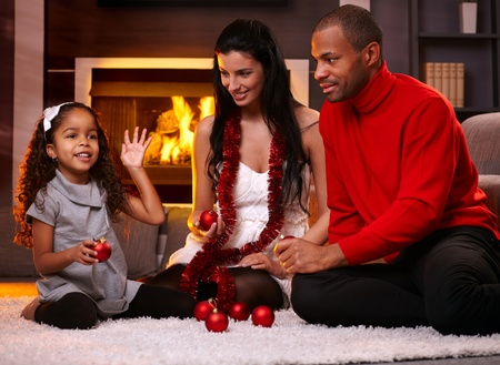 Beautiful diverse family at home in christmas time, sorting christmas decorations. photo