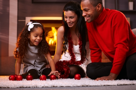 Happy interracial family having fun at home at christmas time, being together, sitting on floor, playing with christmas balls smiling.