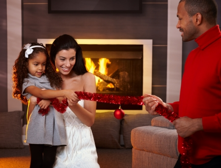 Happy interracial family having fun at home by fireplace, playing with christmas decorations. photo