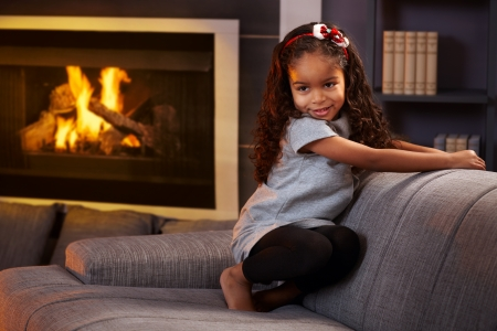 Beautiful afro little girl squatting on sofa in living room, smiling impishly. photo