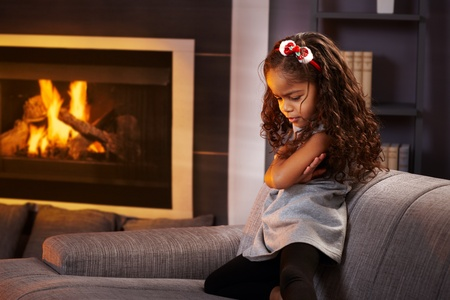 Sulky little afro girl in living room by fireplace. photo