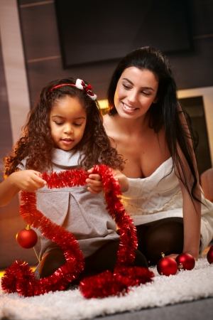 Happy mother and ethnic daughter at christmas time, smiling, playing with decorations. photo