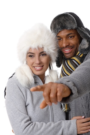 Portrait of young interracial loving couple at wintertime, man pointing to the distance, both smiling. photo