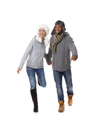 Happy mixed couple running, wearing warm clothes at wintertime. photo