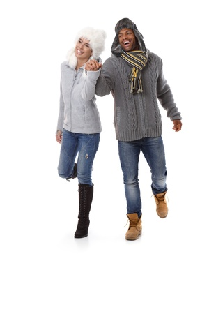 interracial couple: Young interracial couple walking hand in hand at wintertime, smiling. Stock Photo