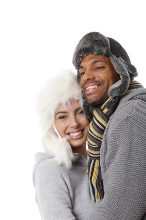 Interracial happy couple embracing at winter, wearing hat, both smiling.   lng . photo