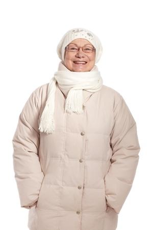 warm clothes: Felice donna anziana in vestiti caldi in inverno in piedi, con le mani in tasca.