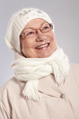 warm clothes: Inverno ritratto di donna anziana felice in vestiti caldi, guardando lontano.