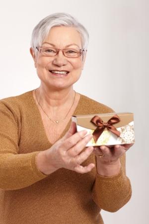 damas antiguas: Señora mayor feliz que sostiene una pequeña caja regalo de lujo.