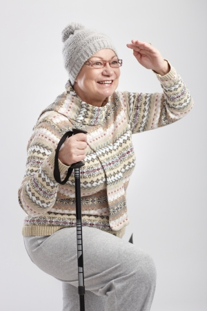 Elderly lady looking to distance, holding hiking poles, smiling. photo