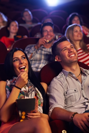 movies: Young couple sitting in cinema, watching movie, eating popcorn, smiling.