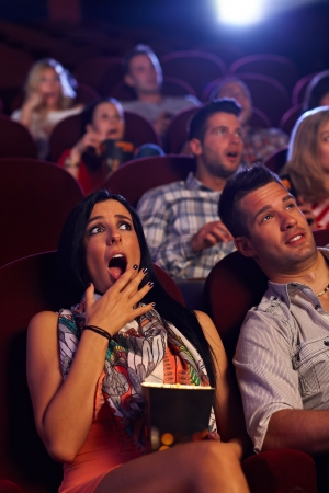 Young woman watching horror movie at cinema, looking shocked, holding popcorn in hand. photo