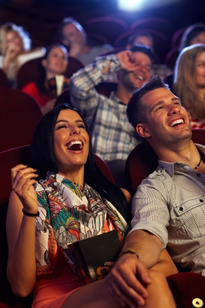funny movies: Happy couple watching comedy in movie theater, laughing.