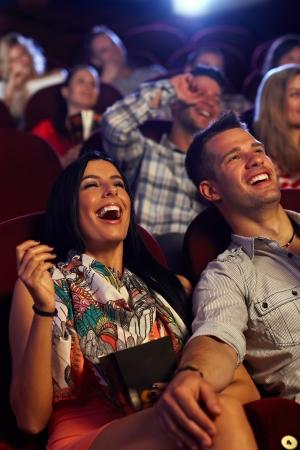 riendo: Pareja feliz viendo la comedia en cine, riendo.