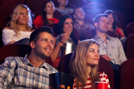 theater audience: Young people sitting at auditorium of movie theater, watching movie. Stock Photo