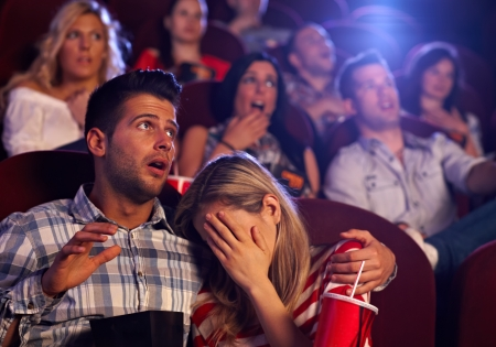 Young couple watching horror movie in cinema, girl turning her head away with fear. photo