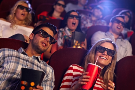 Young people sitting at cinema, watching 3D film, smiling. photo