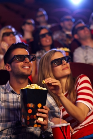 Happy couple sitting in auditorium of 3D movie, eating popcorn. photo