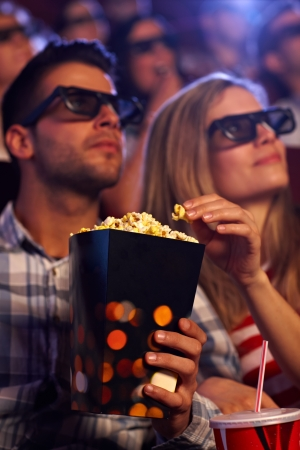 eating popcorn: Young couple eating popcorn in multiplex movie theater, watching 3D movie. Focus on popcorn. Stock Photo