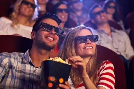 Feliz pareja sentada en la sala de cine, ver películas en 3D, comiendo palomitas de maíz, sonriendo.