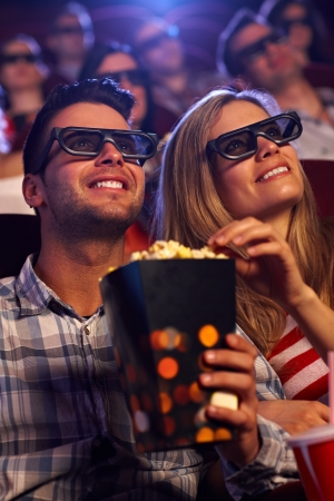 cinema film: Young couple sitting in auditorium of multiplex movie theater, watching 3D movie, eating popcorn, smiling. Stock Photo
