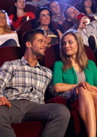 Young couple looking at each other with love, sitting in auditorium of cinema, smiling. photo