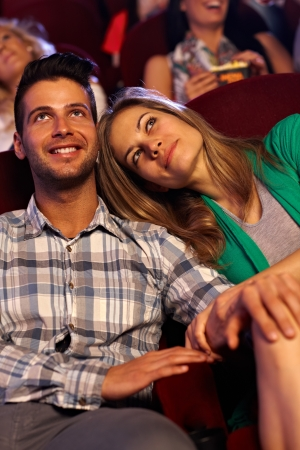 Romantic couple watching movie in cinema, smiling. photo
