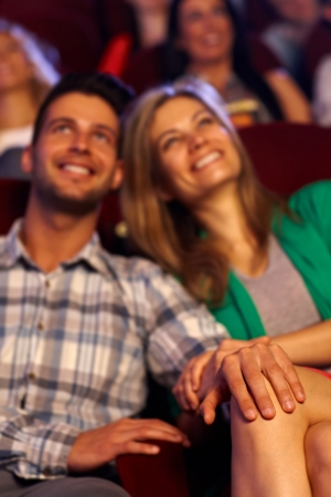 Happy young couple sitting at cinema, focus on hands and female leg. photo