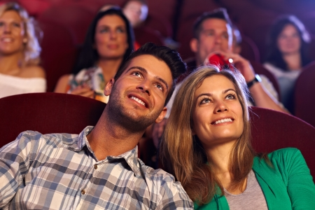 love movies: Happy young couple watching movie in cinema, smiling.