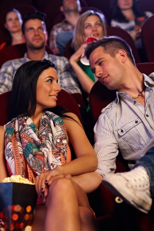 Romantic young couple sitting at movie theater, looking each other with love. photo