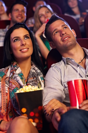 cinema people: Young couple sitting in movie theater, watching film, having popcorn.