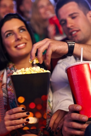 Young couple in multiplex movie theater, eating popcorn. Focus on hands and popcorn. photo
