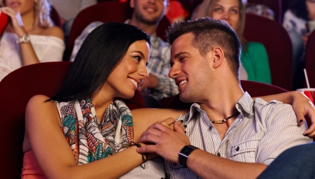be kissed: Attractive loving couple embracing in movie theater, smiling happy.