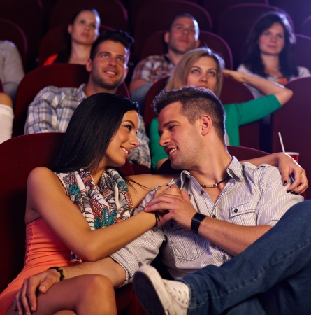 Loving young couple embracing, kissing in movie theater. photo