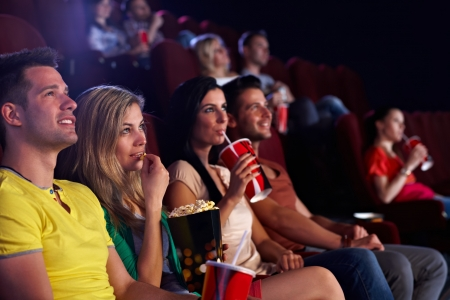 Young people sitting in multiplex movie theater, watching movie, eating popcorn. photo